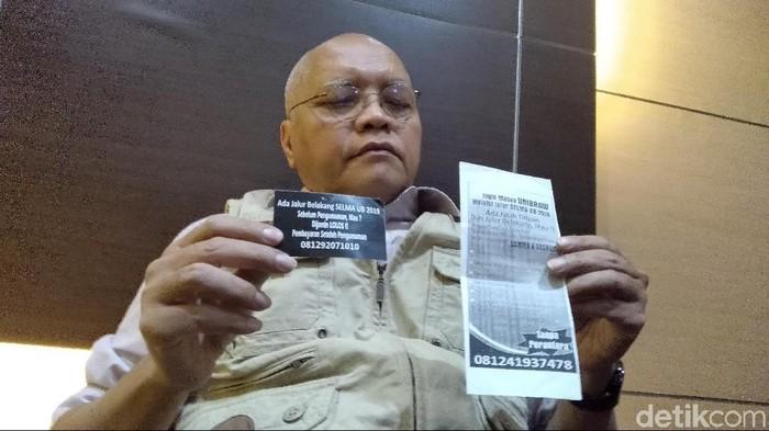 Prija Djatmika menunjukkan brosur dan stiker yang dibagikan sindikat calo/Foto file: Muhammad Aminudin