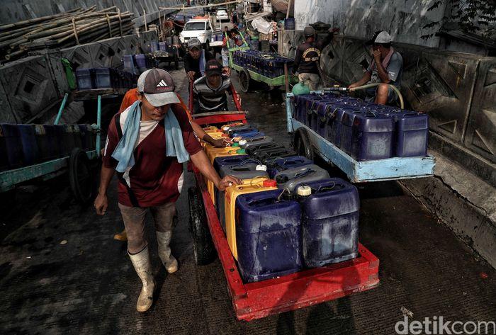 Sejumlah pedagang air bersih keliling menjajakan dagangannya di kawasan Muara Angke, Jakarta Utara, Senin (22/7/2019).