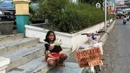 Berjualan Kue Sambil Gendong Adiknya, Anak Ini Bikin Haru Netizen
