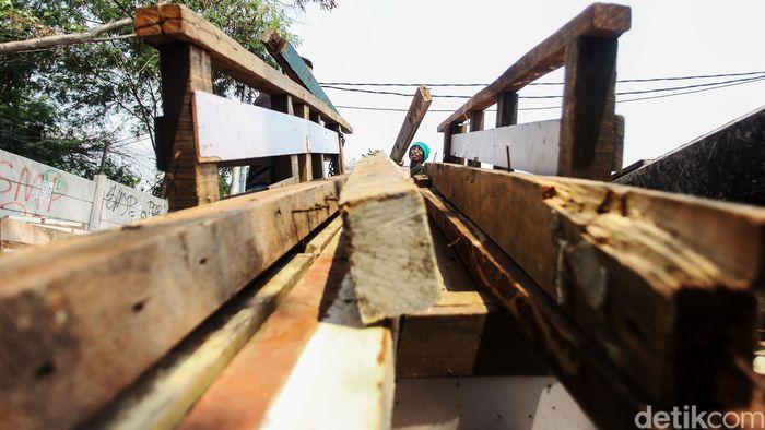 Seorang pengepul kayu bekas tengah merapihkan kayu miliknya, Senin (22/7).