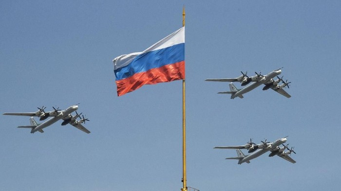 FILE - In this file photo taken on Friday, May 4, 2018, Russian Tu-95 strategic bombers fly past the Russian flag on the Kremlin complex during a rehearsal for the Victory Day military parade in Moscow, Russia.  South Korean air force jets fired 360 rounds of warning shots after a Russian military plane briefly violated South Koreas airspace twice on Tuesday, Seoul officials said, in the first such incident between the two countries. (AP Photo/Pavel Golovkin, File)