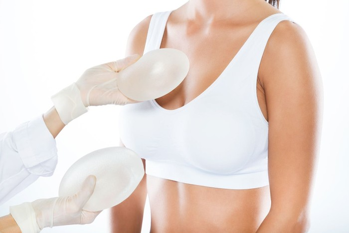 Portrait of female doctor choosing mammary prosthesis with her patient over white background.