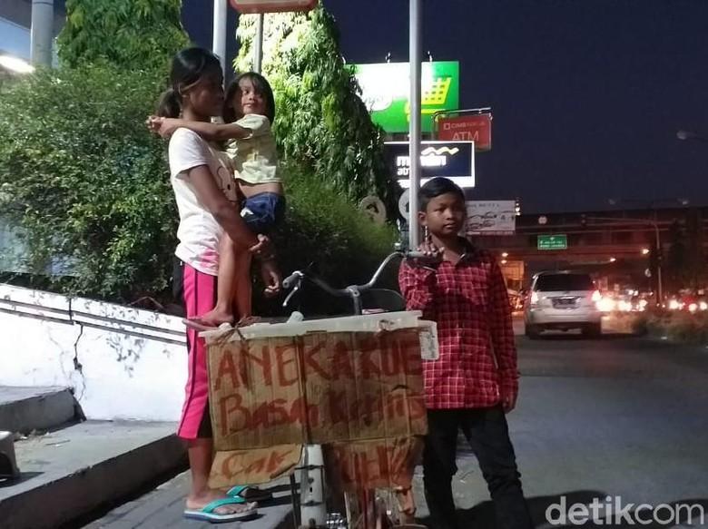 Anak Berjualan Kue Sambil Gendong Adik di Surabaya Viral di Medsos
