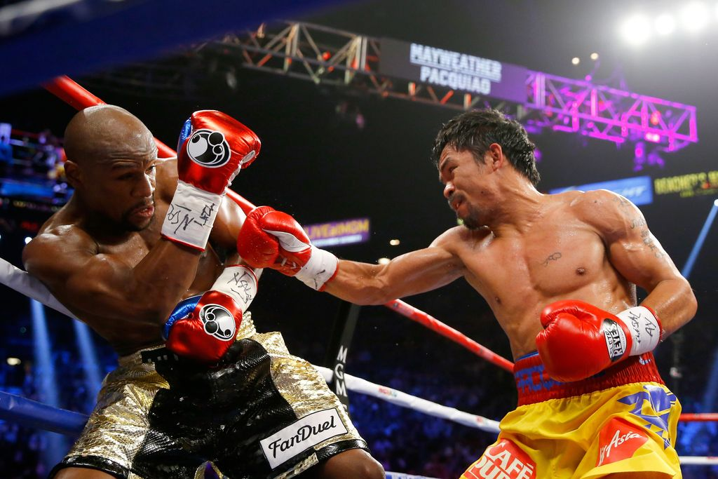 LAS VEGAS, NV - MAY 02:  Manny Pacquiao throws a right at Floyd Mayweather Jr. during their welterweight unification championship bout on May 2, 2015 at MGM Grand Garden Arena in Las Vegas, Nevada.  (Photo by Al Bello/Getty Images)
