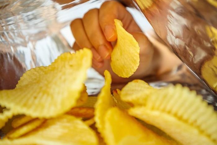 Close up of mens hand grabbing chips