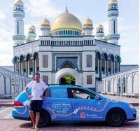Gayanya berfoto dengan mobil listriknya di Bandar Seri Begawan, Brunei. (plugmeintravel/Instagram)