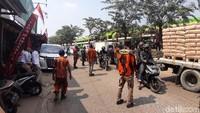 Anggota ormas lainnya mengatur laju kendaraan yang berada di depan gang tersebut.