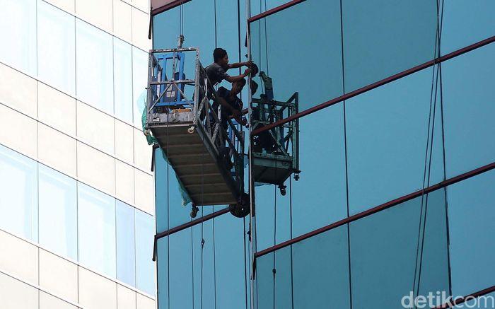 Tanpa helm dan alat keselamatan diri lainnya, para pekerja membersihkan gedung-gedung bertingkat di Jakarta.