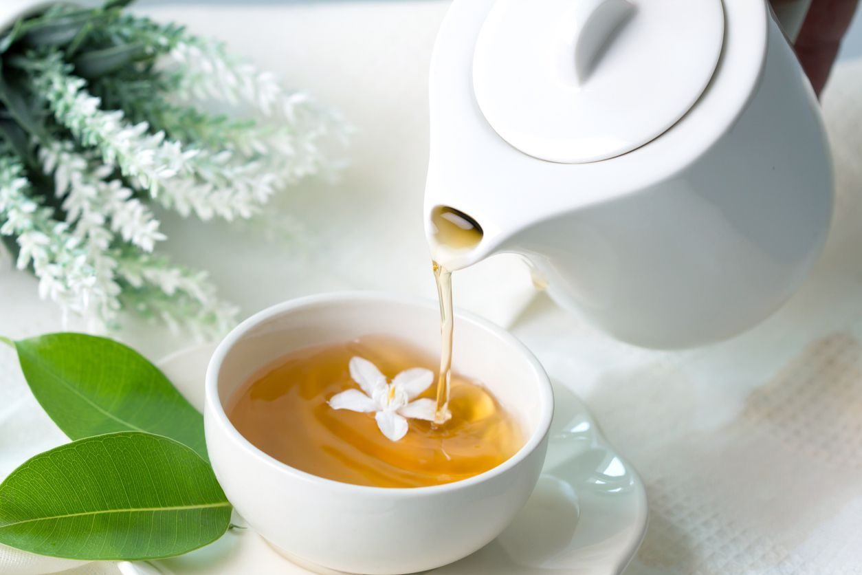 Close up pouring hot jasmine tea in a white tea cup ,  Tea ceremony time concept