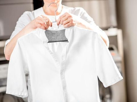 Senior washwoman hanging a shirt on the hanger standing in the professional laundry