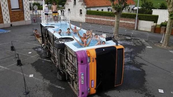 Ini bus kota yang bernama le bus piscine karya seniman Prancis Benedetto Bufalino. Bus ini menjadi kolam renang di Gosnay dekat Bethune, Prancis. (REUTERS / Pascal Rossignol)