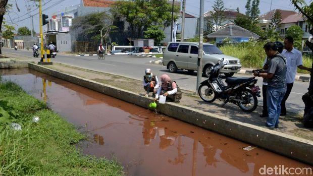 Petugas mengambil sampel air sungai yang tercemar pewarna batik di Kota Pekalongan.