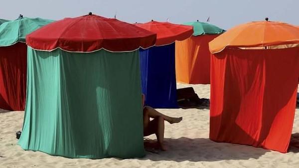 Di Deauville, Prancis, para wanita bersantai di pantai dengan suhu 38 derajat dengan menggunakan tenda seperti ini. (REUTERS/Kevin Coombs TPX IMAGES OF THE DAY)