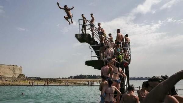 Masih di Brittany, Prancis, para kawula muda mengantre untuk lompat ke dalam kolam di Saint-Malo. (Valery HACHE/AFP)