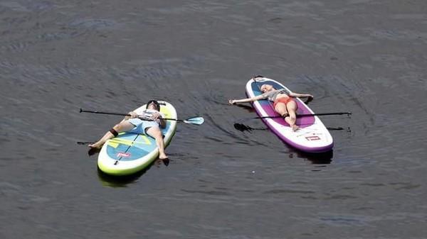 Kalau warga Berlin lain lagi. Mereka menikmati suasana ekstrem dengan main kano di Sungai Spree. Mainnya sampai ketiduran gitu ya? (REUTERS/Fabrizio Bensch)