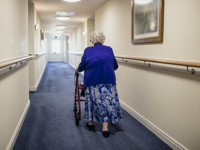 A senior woman walking down a corridor with the assistance of a walker. view from rear