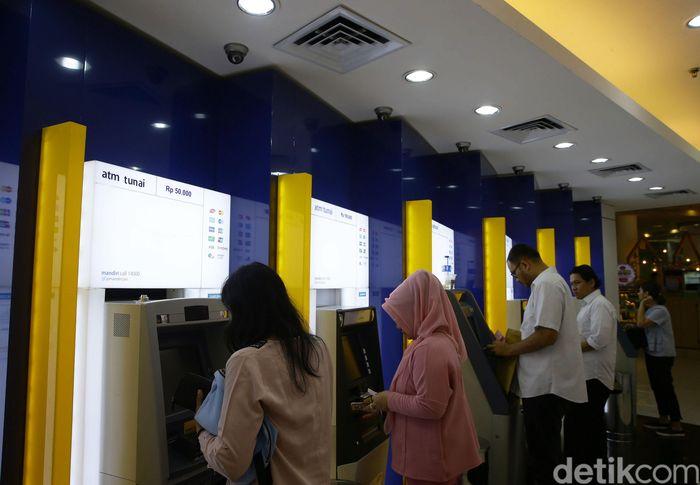 Warga menarik uang tunai dari mesin anjungan tunai mandiri (ATM) di salah satu galeri di kawasan Kebayoran Lama, Jakarta, Senin (5/8/2019).