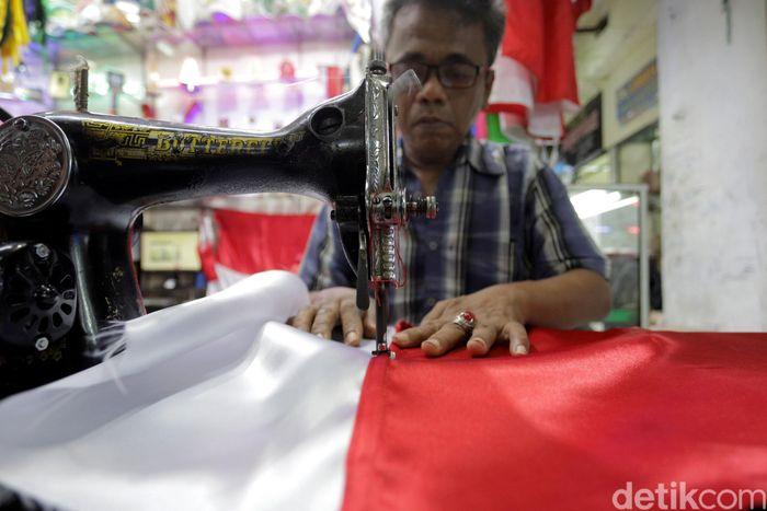 Seorang penjahit di Pasar Senen, Jakarta, tengah sibuk mengerjakan orderan bendera merah putih yang meningkat jelang HUT RI ke-74, Selasa (6/8/2019).