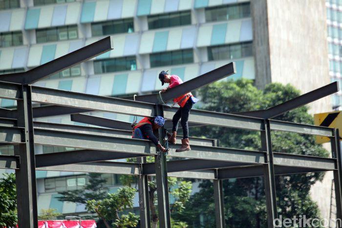 Beberapa pekerja sedang menyelesaikan pembangunan Halte TransJakarta di Tosari, Jalan Thamrin, Jakarta Pusat.
