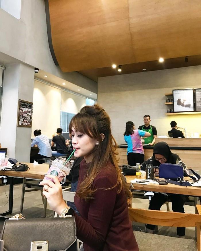 Wanita yang tinggal di Medan ini juga penggemar kopi. Ia tampak santai menyeruput segelas kopi di kafe kopi kekinian. Foto: instagram @niaaprilsllh
