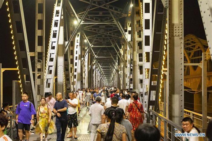 Orang-orang terlihat di atas jembatan rel Sungai Songhuajiang yang telah direnovasi di Harbin, ibu kota Provinsi Heilongjiang, China timur laut.Foto: Dok. Xie Jianfei/Xinhua