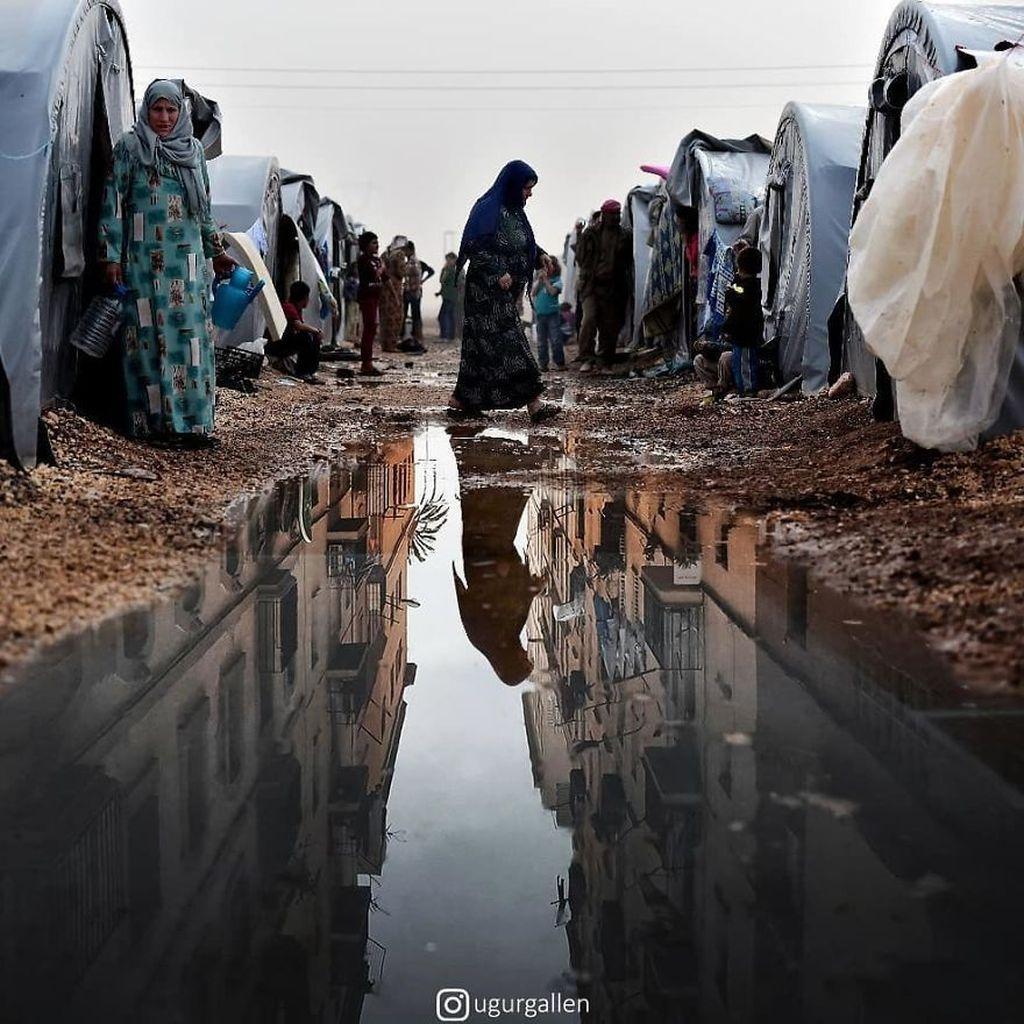 Seorang wanita berjalan melewati tenda di sebuah kamp pengungsi Suriah di kota Suruc, provinsi Sanliurfa, Turki Foto: Uğur Gallenkuş