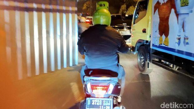 Pengendara motor mengenakan helm mirip tabung elpiji