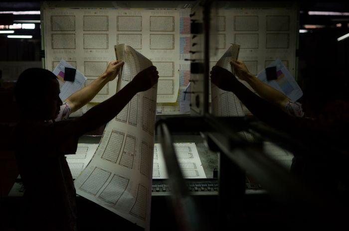 Seorang petugas sedang memeriksa huruf hijaiyah saat pencetakan kitab suci Alquran di PT Sygma Examedia, Bandung, Jawa Barat, Senin (12/8/2019).