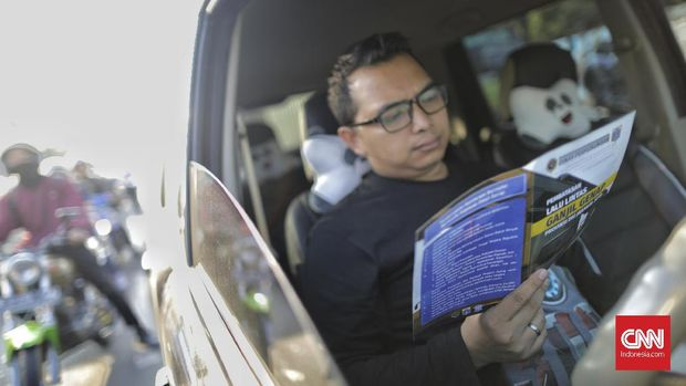 Pengendara membaca selebaran sosialisasi ganjil genap.