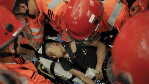 Petugas medis mengevakuasi pria yang diklaim polisi China yang menyamar oleh para demonstran Hong Kong