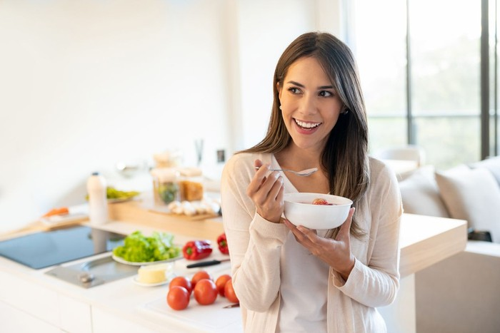 Portrait of a casual woman at home eating a healthy breakfast and looking happy - lifestyle concepts