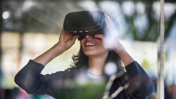 Young woman looking with VR behind the glass
