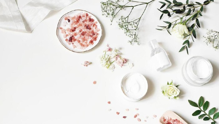 Styled beauty corner, web banner. Skin cream, tonicum bottle, dry flowers, leaves, rose and Himalayan salt. White table background. Organic cosmetics, spa concept, empty space. Flat lay, top view