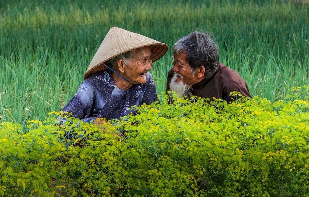 Potret sepasang kakek dan nenek yang tengah tertawa di sebuah kawasan di Vietnam. Istimewa/Agora Images/@diepvan via Boredpanda.