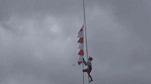 Siswa SD di Ambon membetulkan pengait Bendera Merah Putih, Sabtu (17/8/2019)