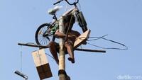 Seorang peserta berhasil meraih puncak pohon pinang.