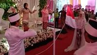 Pernikahan mereka pun menjadi viral di media sosial lantaran didahului dengan upacara bendera sebelum akad nikah digelar.