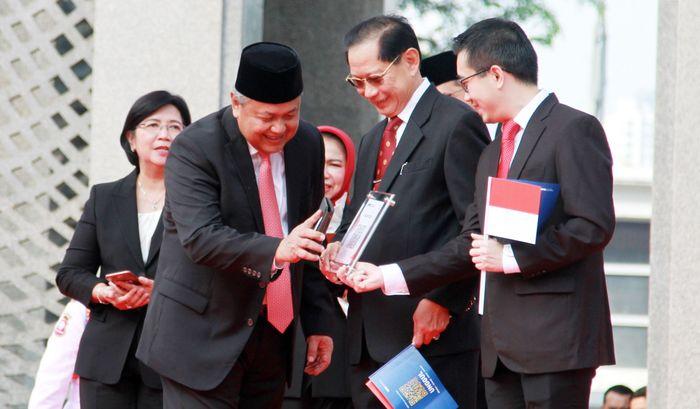 Gubernur Bank Indonesia (BI) Perry Warjiyo (kiri) dan Presiden Direktur BCA Jahja Setiaatmadja (tengah) melakukan experience transaksi menggunakan QR Code Indonesia Standard (QRIS) di tengah launching QRIS di Jakarta, Sabtu (17/08). Istimewa