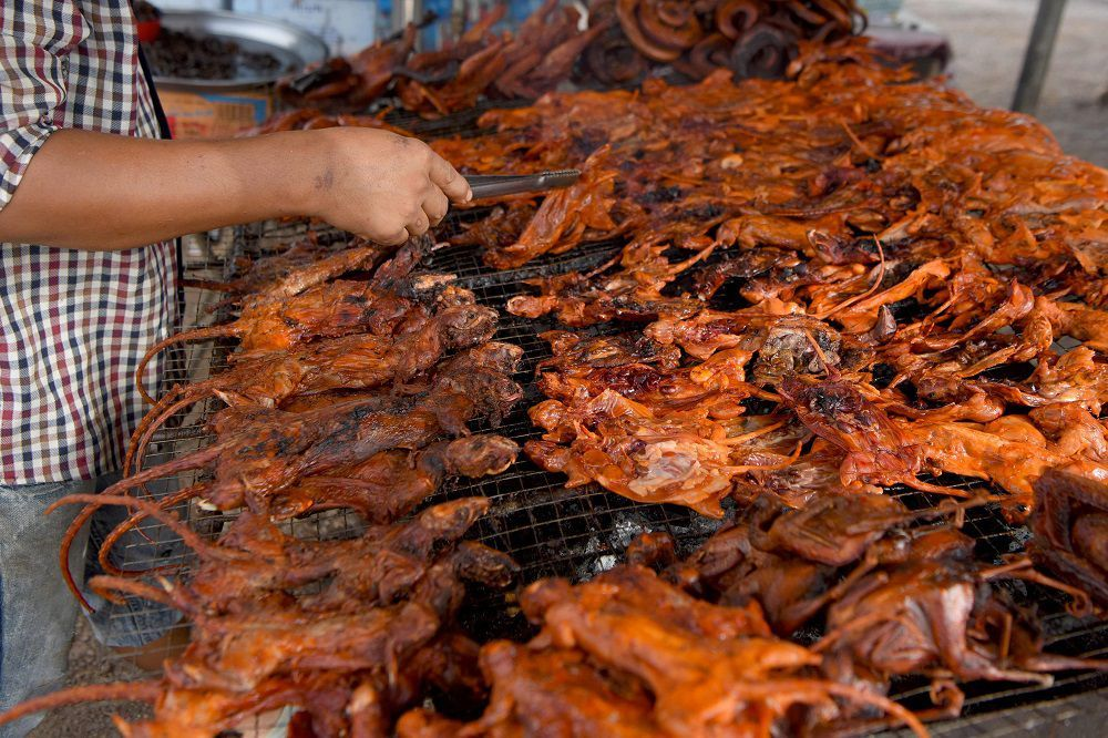This photo taken on August 10, 2019 shows a man grilling rats at a stall in Battambang province. - Barbecued field rats are not everybody's idea of a tasty treat, but in Cambodia's rural Battambang province they are popular as a cheap - and quick - snack, with small skewered ones going for 0.25USD each while larger rodents can cost 1.25USD. (Photo by TANG CHHIN Sothy / AFP)