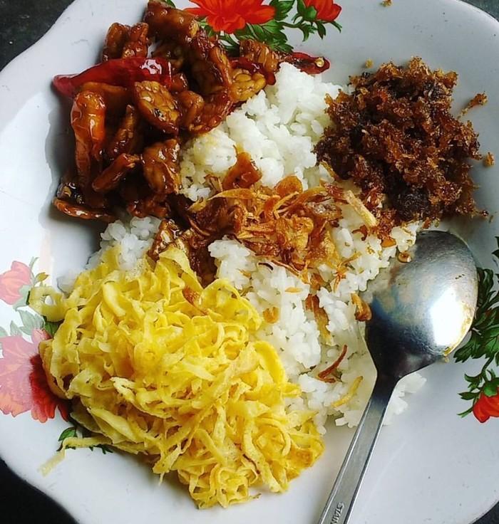 Di beberapa kota di Jawa Tengah, nasi langgi jadi sarapan enak. Nasi putih diberi lauk irisan dadar telur, orek tempe, secuil dendeng sapi dan sambal plus mentimun. Murah meriah dan sedap. Foto : Instagram @kastuti_diehardja
