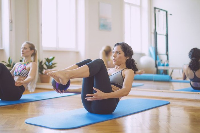 Young sporty attractive woman doing toning pilates exercise for abs, balance Paripurna Navasana pose with pilates magic circle in hands, working out wearing sportswear, indoor full length, yoga studio