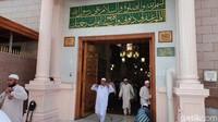 Gerbang di makam Nabi Muhammad didominasi dengan ukiran kaligrafi berwarna emas. Di dalam rongga kaligrafi itu, terlihat remang-remang suasana bagian dalam yang besar.