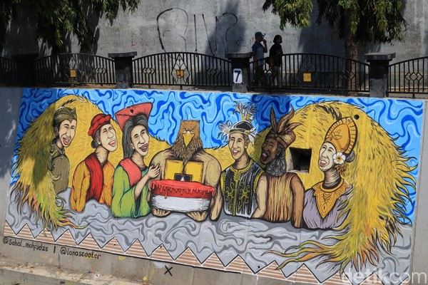 Pejalan kaki yang melintasi bantaran Kali Pepe beserta mural Indonesia (Randy/detikcom)