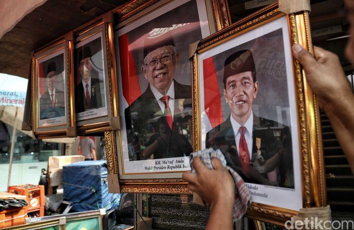 Seorang pedagang memperlihatkan poster Presiden Joko Widodo dan Wakil Presiden Maruf Amin periode 2019-2024.