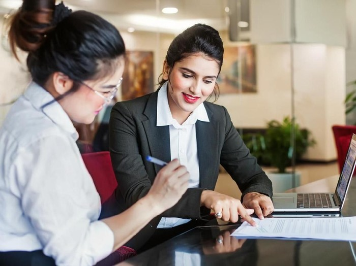 Indian female agent helping client sign the application document