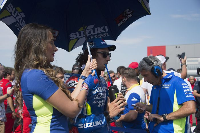 Alex Rins didampingi umbrella girl dengan seragam biru khas Suzuki. Rins menjalani balapan spesial di MotoGP Inggris setelah menjadi juara (Mirco Lazzari gp/Getty Images)