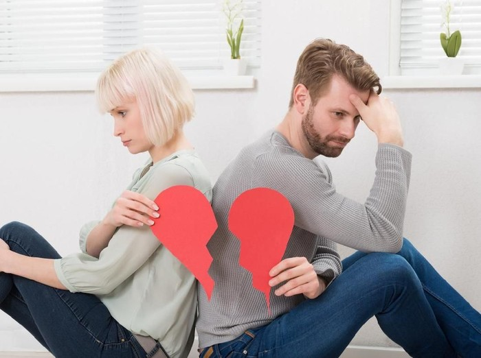 Sad Couple Sitting Back To Back Holding Red Broken Heart