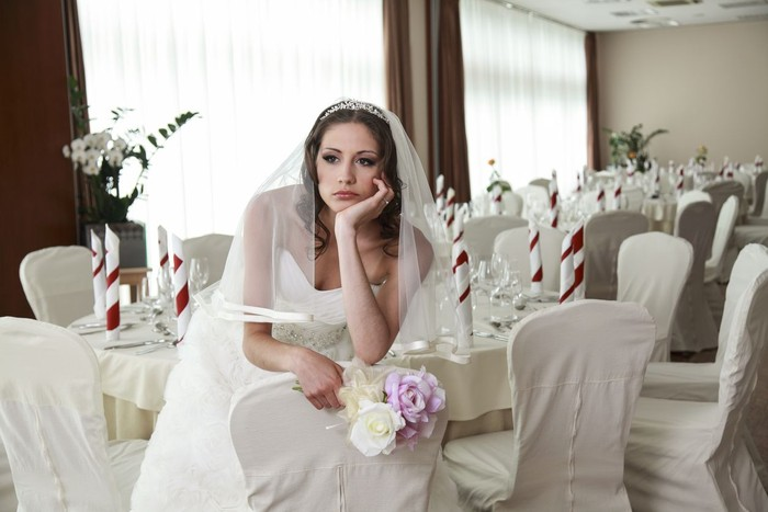 Bride sitting in a ceremony waiting restaurant. Sitting sad with head and flowers in her hands.