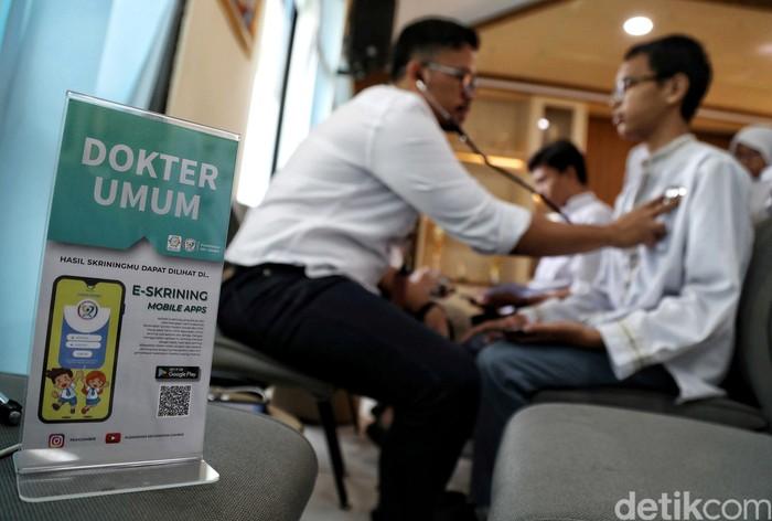 Seorang siswa tengah melakukan pemeriksaan kesehatan di SMKN 2, Jakarta, Jumat (30/8/2019). Puskesmas Kecamatan Gambir, melalui inovasi GKM Manja tahun 2019 mengembangkan aplikasi e-Skrining yang digunakan untuk skrining usia sekolah dan remaja.