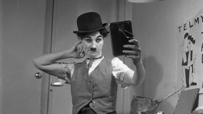 1955:  Austrian actress and impersonator Telmy Talia checks her make-up after her uncanny transformation into Charlie Chaplin for a Paris nightclub show.  (Photo by Michel Brodsky/BIPs/Getty Images)